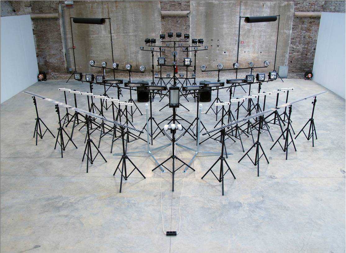 Idan Hayosh - SU-22 display, 2009. Sound Installation. Formation of high wattage Strobe lights. bursts of of flickering light and electric current sound are heard and  seen. Lamps are triggered by motion sensors.